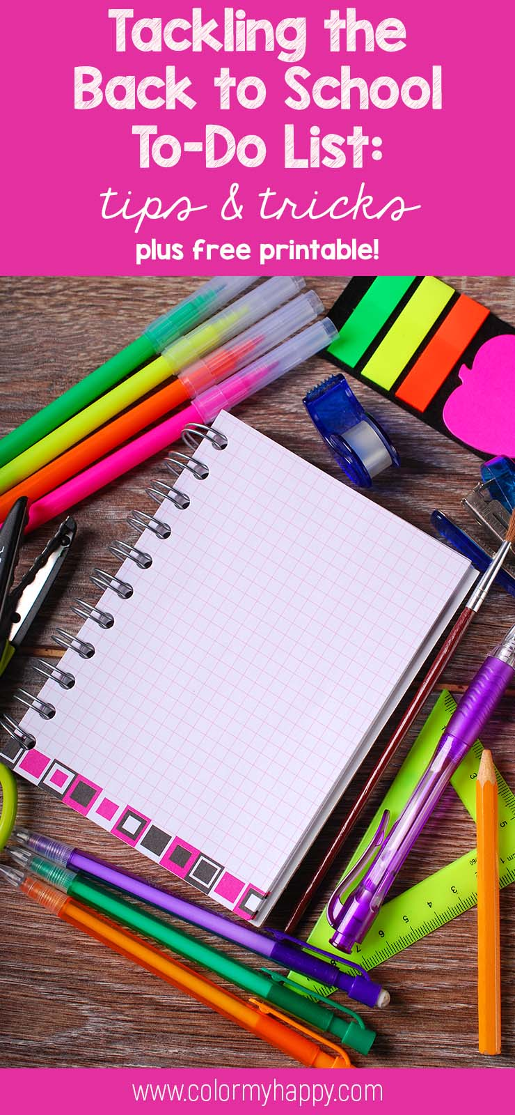 A notebook, tape, stapler, pens, scissors, post-its, and markers on a table.