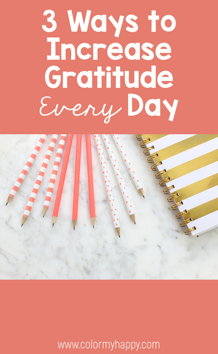 "Coral and white pencils and a gold and white notebook on a gray and white marble countertop with the words ""3 Ways to Increase Gratitude Every Day"""
