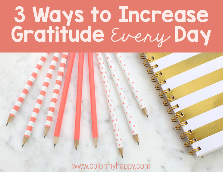 "Coral and white pencils and a white and gold notebook on a gray and white marble countertop with the words ""3 Ways to Increase Gratitude Every Day"""
