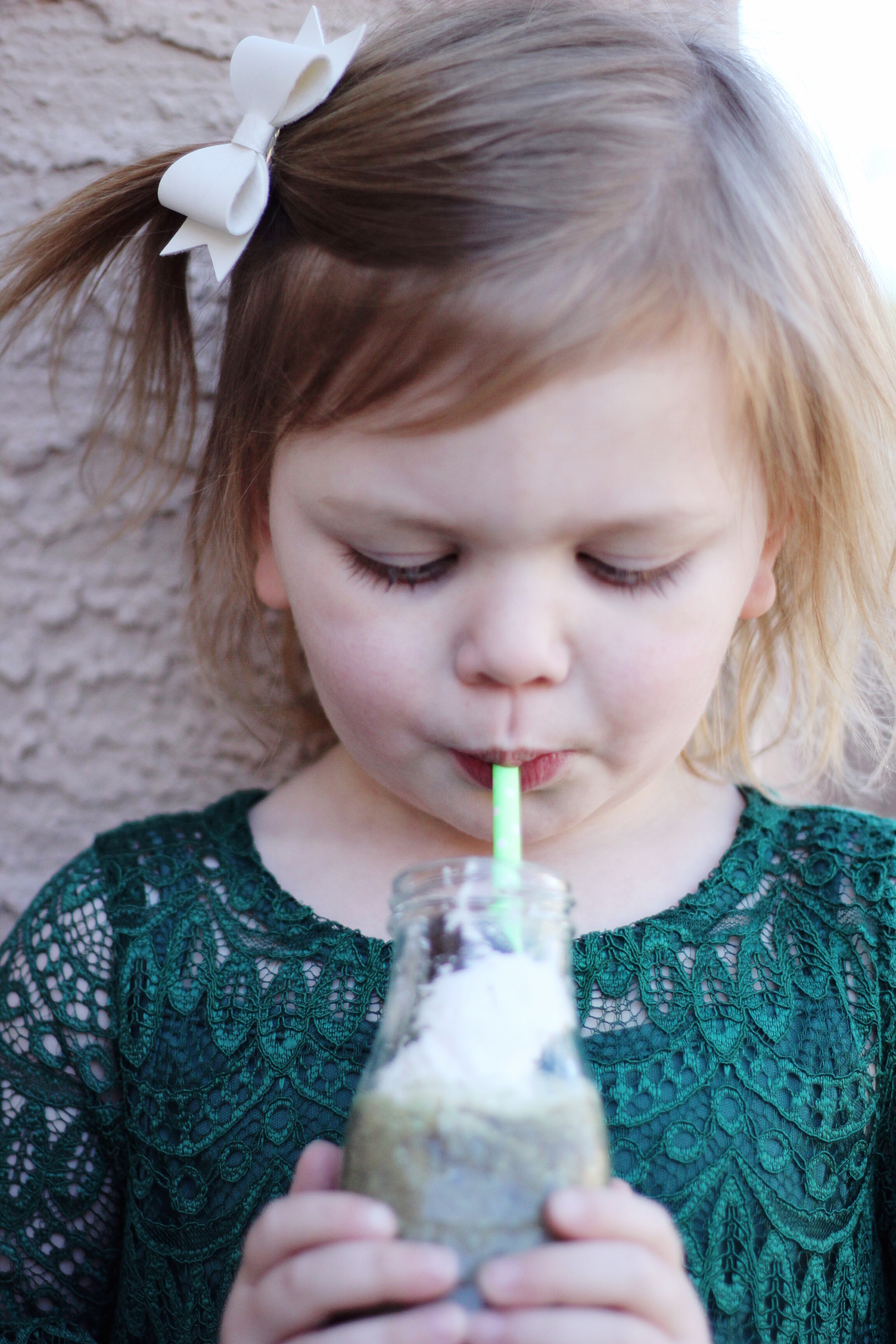 A little girl looking down at her shamrock shake