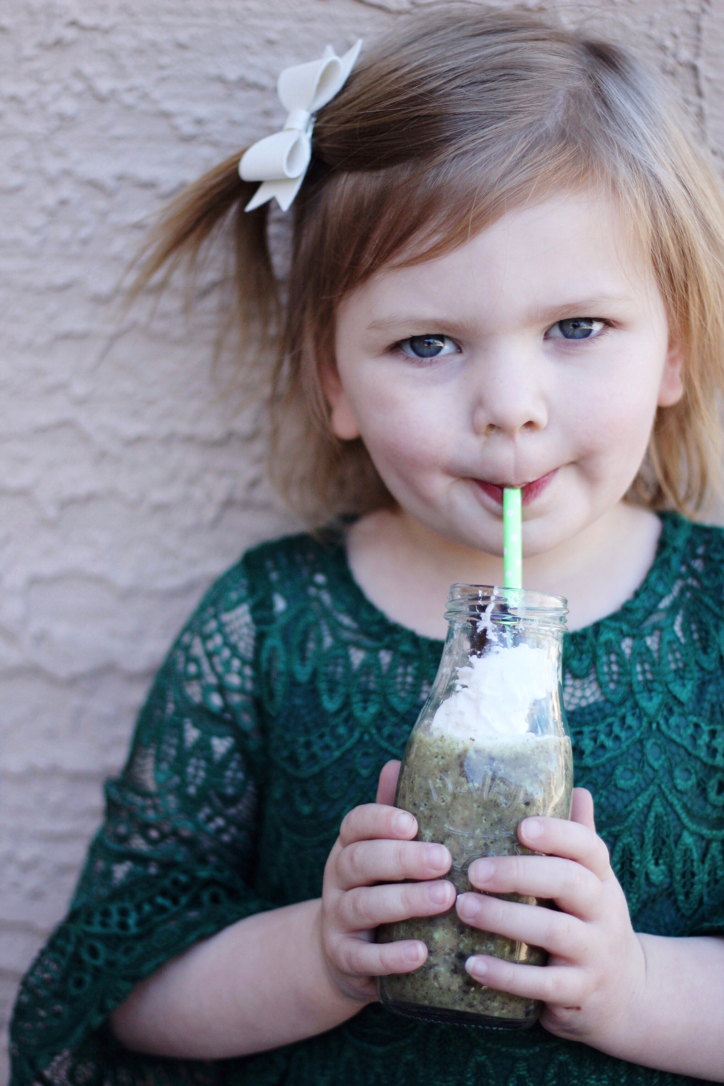 A close up of a little girl smiling while drinking a shamrock shake