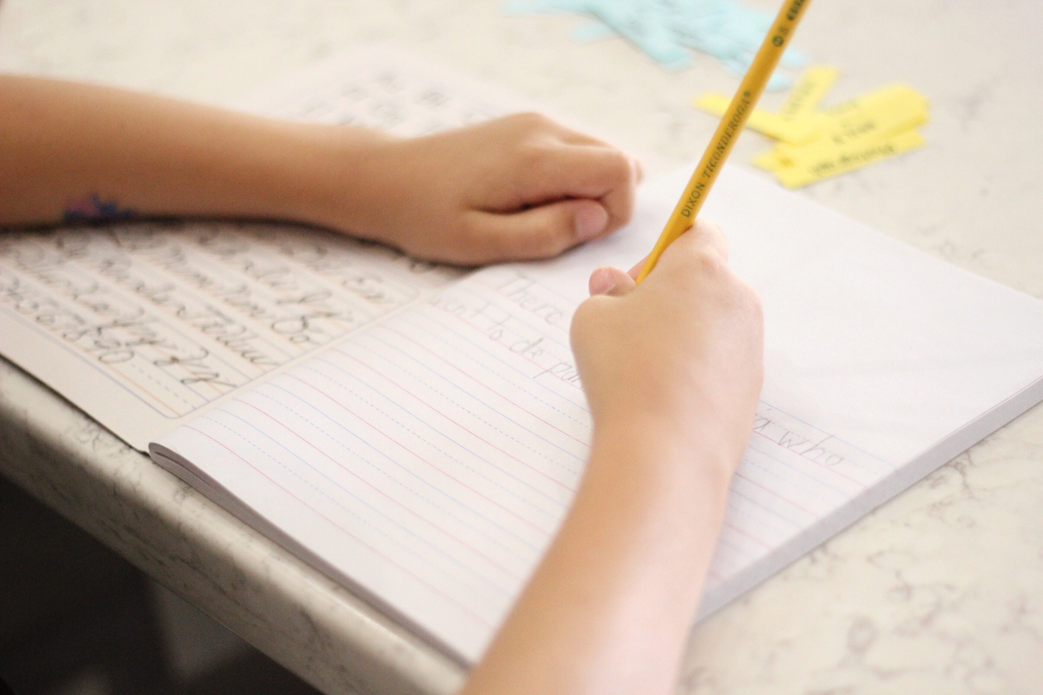 A boy\'s hands writing in a notebook.