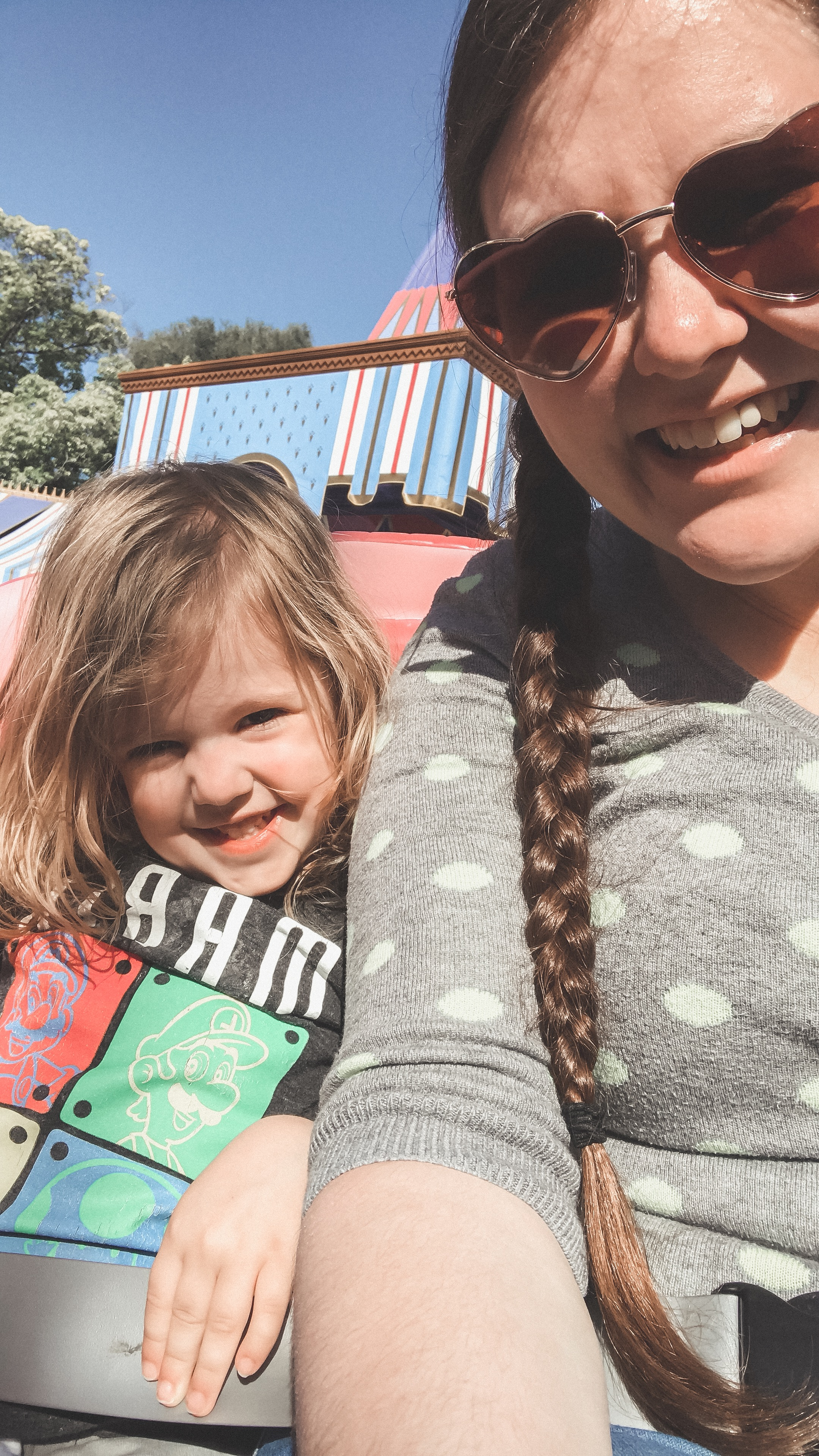 A girl wearing sunglasses with her daughter taking a selfie