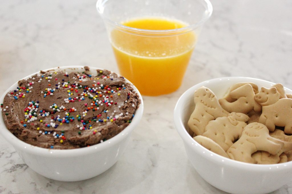 A close up of a bowl of animal crackers, a bowl of chocolate sprinkle dip, and a cup of orange juice.