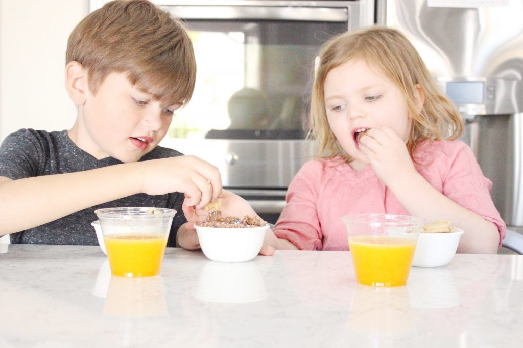 A little boy and girl sitting at a table with a cup of orange juice while eating a snack