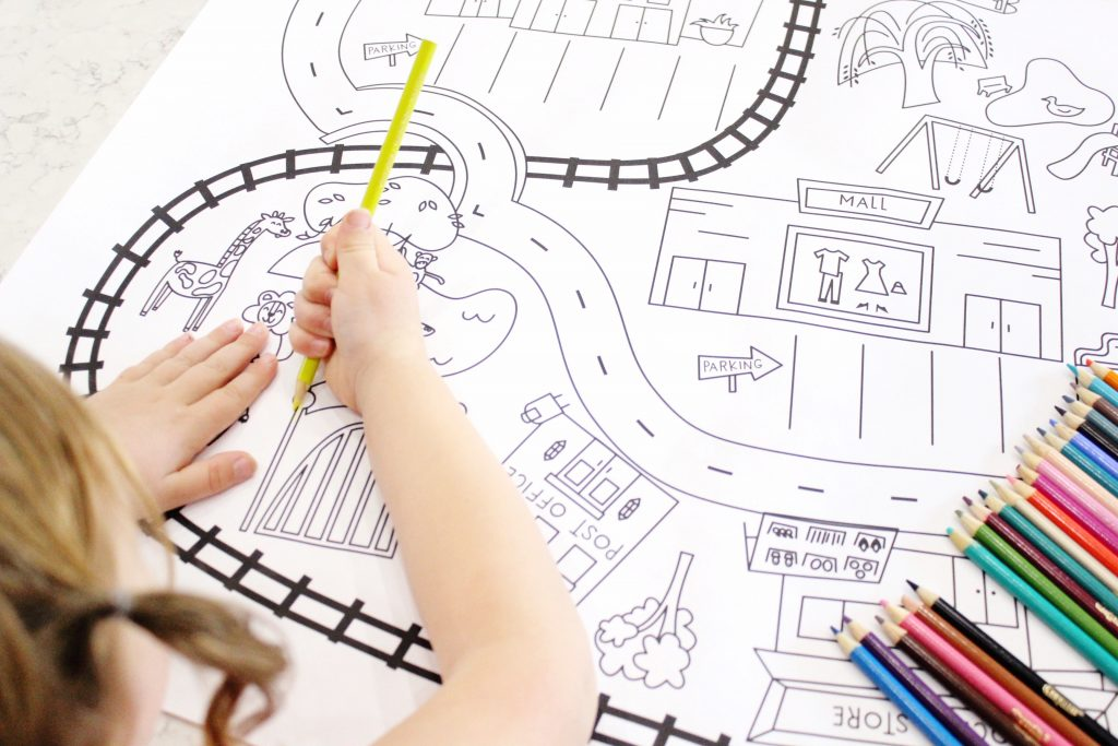 Camp Castle Playmat Printable Giant City Coloring Sheet being colored by a child with a colored pencil