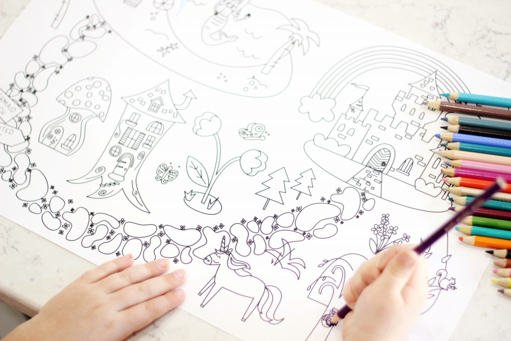 Camp Castle Playmat Printable Rainbow Land Coloring Sheet being colored by a child with a colored pencil